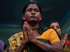 "Champa, 45, has colour applied on her face as she prays with others on the first day of ""Ganesh Chaturthi"" at a temple in Karachi"